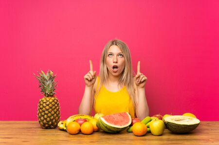 Young blonde woman with lots of fruits pointing with the index finger a great idea