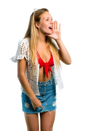 Chica rubia en vacaciones de verano gritando al lateral y anunciando algo sobre fondo blanco aislado