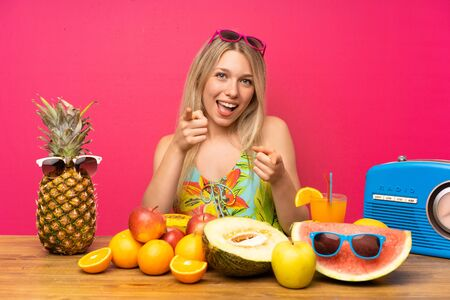 Young blonde woman with lots of fruits points finger at you Imagens