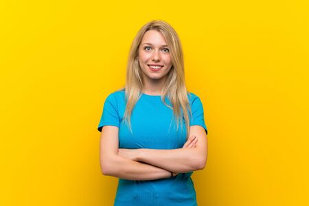 Young blonde woman over isolated yellow background keeping the arms crossed in frontal position Reklamní fotografie