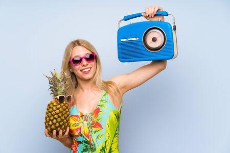 Mujer joven en traje de baño sosteniendo una piña con gafas de sol y una radio
