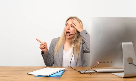 Young woman working with headset surprised and pointing finger to the side