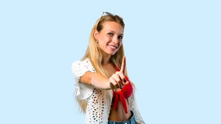 Blonde girl in summer vacation showing and lifting a finger in sign of the best on blue background