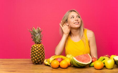Young blonde woman with lots of fruits listening something Banque d'images
