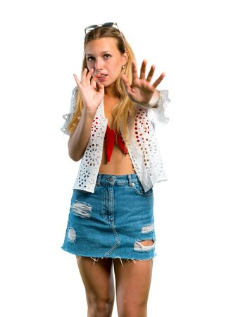 Blonde girl in summer vacation is a little bit nervous and scared stretching hands to the front on isolated white background