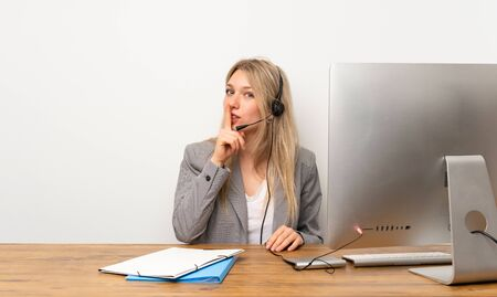 Young woman working with headset doing silence gesture