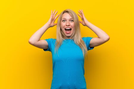 Young blonde woman over isolated yellow background with surprise expression