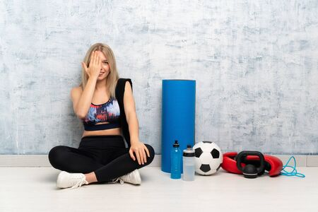 Young blonde sport woman sitting on the floor covering a eye by hand