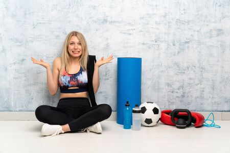 Young blonde sport woman sitting on the floor having doubts with confuse face expression