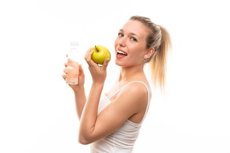 Young blonde woman with an apple and a bottle of water