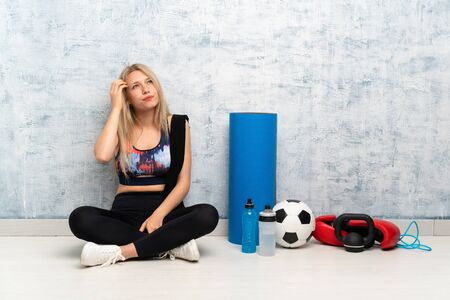 Young blonde sport woman sitting on the floor having doubts and with confuse face expression