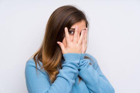 Chica joven con suéter azul que cubre los ojos y mirando a través de los dedos