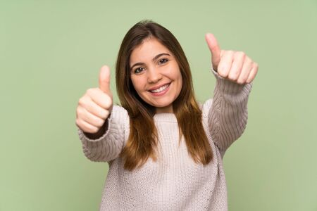 Young girl with white sweater giving a thumbs up gesture 版權商用圖片