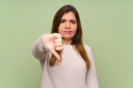 Young girl with white sweater showing thumb down sign Banque d'images
