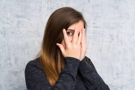 Chica joven sobre la pared del grunge que cubre los ojos y mirando a través de los dedos