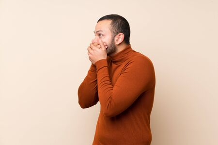 Colombian man with turtleneck sweater covering mouth and looking to the side Standard-Bild