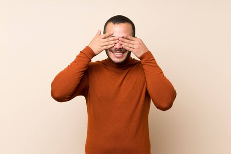 Colombian man with turtleneck sweater covering eyes by hands