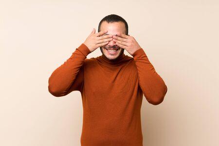 Hombre colombiano con suéter de cuello alto que cubre los ojos con las manos