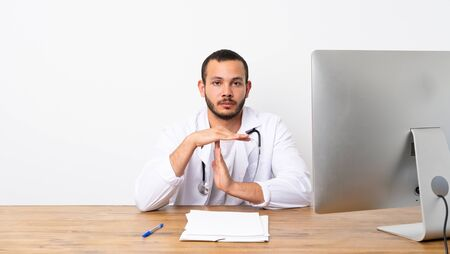 Doctor Colombian man making time out gesture Stock Photo