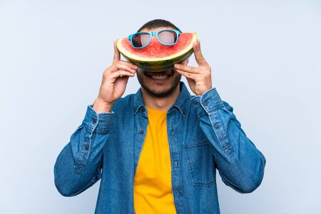 Colombian man holding a watermelon with sunglasses