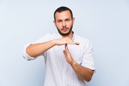 Colombian man over isolated blue wall making time out gesture