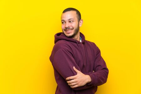 Colombian man with sweatshirt over yellow wall with arms crossed and happy