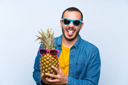 Colombian man holding a pineapple with sunglasses showing tongue at the camera having funny look