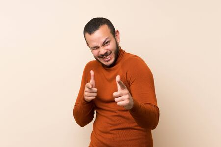 Colombian man with turtleneck sweater pointing to the front and smiling