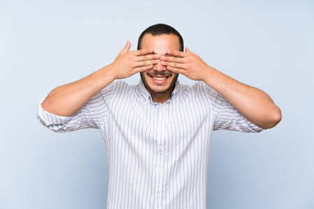 Colombian man over isolated blue wall covering eyes by hands