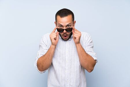 Colombian man over isolated blue wall with glasses and surprised