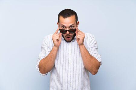 Uomo colombiano sopra il muro blu isolato con gli occhiali e sorpreso