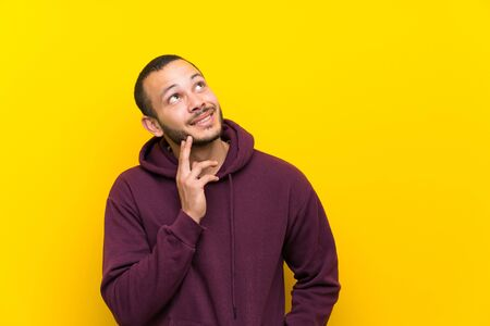 Colombian man with sweatshirt over yellow wall thinking an idea while looking up 免版税图像