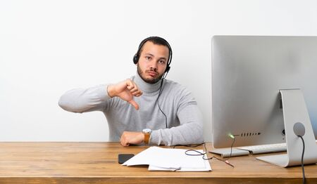 Telemarketer Colombian man showing thumb down with negative expression