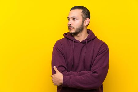 Colombian man with sweatshirt over yellow wall portrait