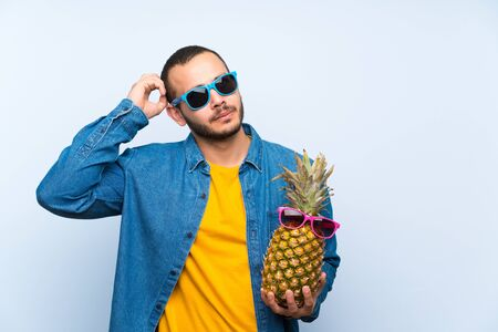 Colombian man holding a pineapple with sunglasses thinking an idea