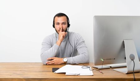 Telemarketer Colombian man showing a sign of silence gesture putting finger in mouth
