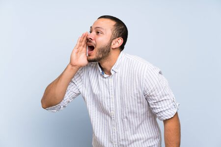 Colombian man over isolated blue wall shouting with mouth wide open to the lateral Stock fotó