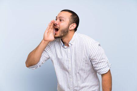 Kolumbianischer Mann über isolierter blauer Wand, der mit weit geöffnetem Mund zur Seite schreit Standard-Bild