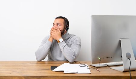 Telemarketer Colombian man covering mouth and looking to the side