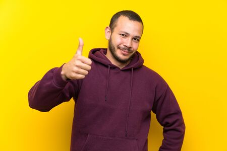Colombian man with sweatshirt over yellow wall with thumbs up because something good has happened