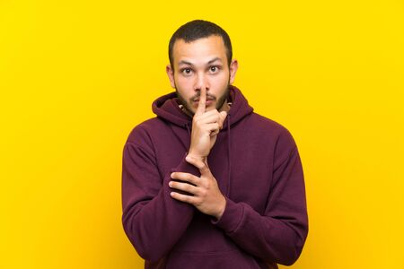 Colombian man with sweatshirt over yellow wall showing a sign of silence gesture putting finger in mouth Standard-Bild