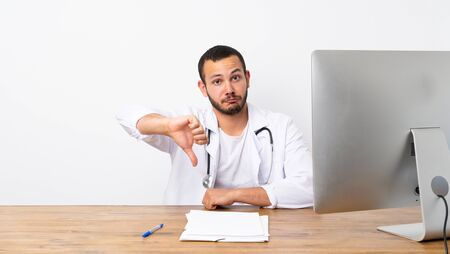 Doctor Colombian man showing thumb down with negative expression