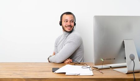 Telemarketer Colombian man with arms crossed and happy
