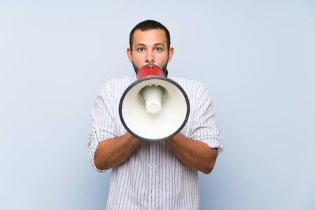 Kolumbianischer Mann über isolierter blauer Wand, der durch ein Megaphon schreit Standard-Bild