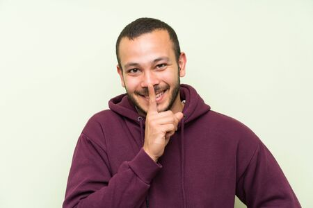 Colombian man with sweatshirt over green wall doing silence gesture