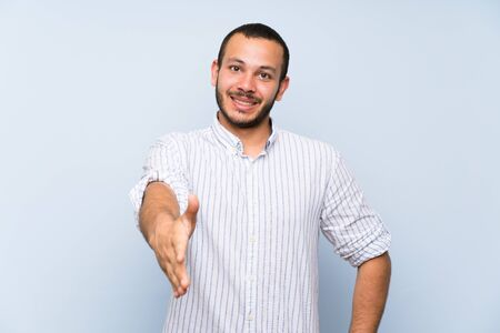 Colombian man over isolated blue wall shaking hands for closing a good deal