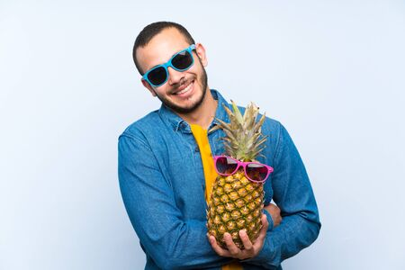 Colombian man holding a pineapple with sunglasses keeping arms crossed