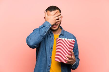 Colombian man with popcorns covering eyes by hands