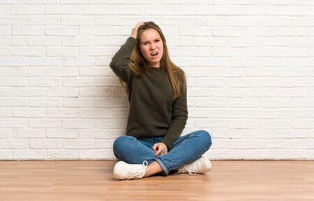Young woman sitting on the floor with an expression of frustration and not understanding Stockfoto