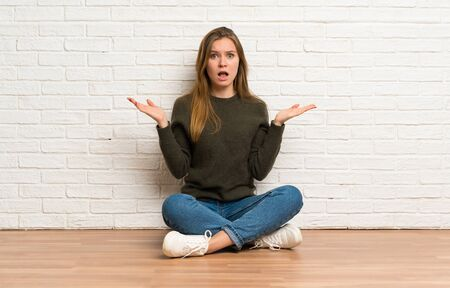 Young woman sitting on the floor making doubts gesture Stockfoto - 128616335